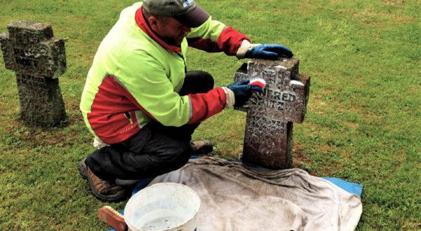 Mit Bürste, Wasser und Reinigungsmittel entfernt Rizo Zahitovic die Verschmutzungen an den Steinkreuzen Foto: Helmut Gleuel